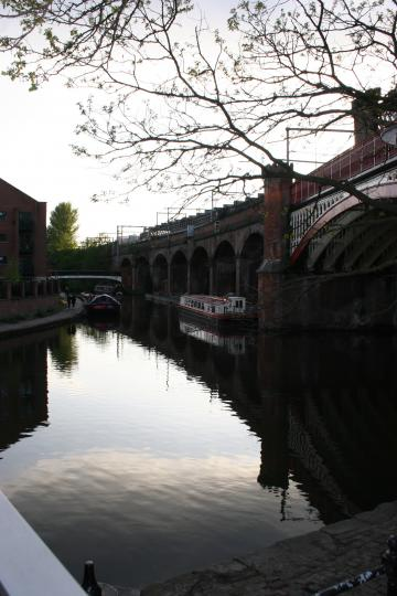 A view of one of Manchesters canals with narrow boat and viaduct